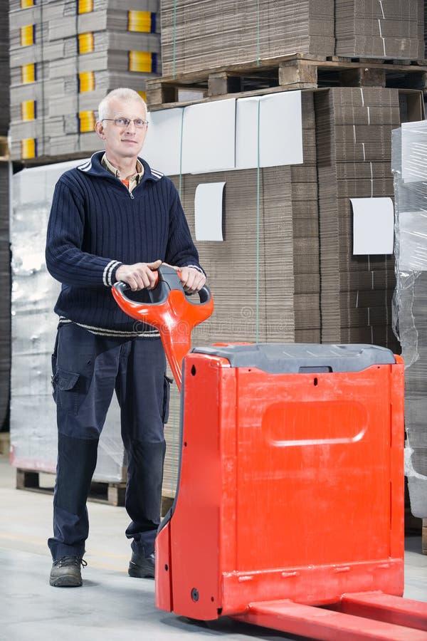 Trabajador que se coloca con Handtruck en Warehouse imagen de archivo libre de regalías