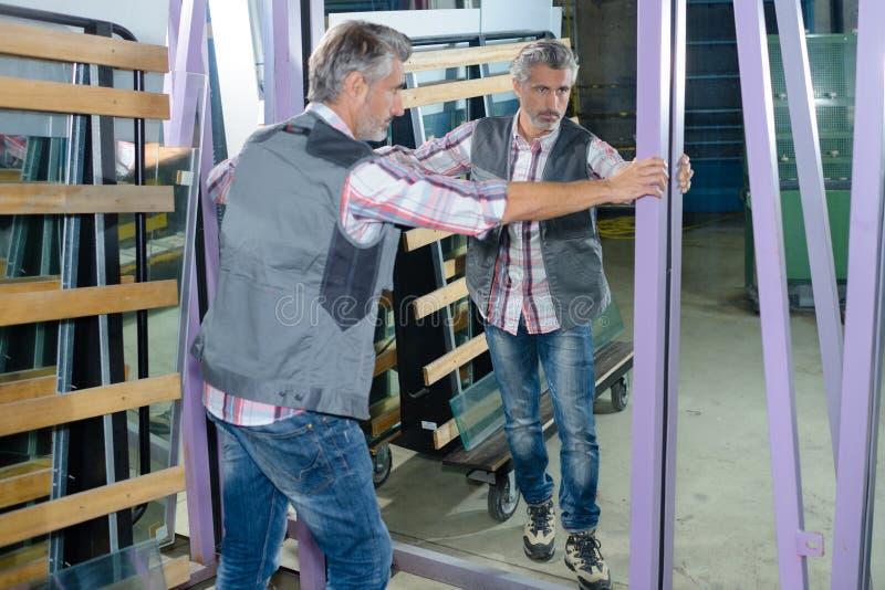 Trabajador que sostiene el espejo de la pared fotos de archivo