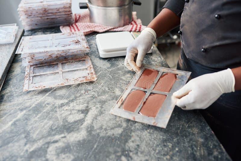 Trabajador que sostiene un molde de la barra por completo del chocolate derretido fotos de archivo libres de regalías