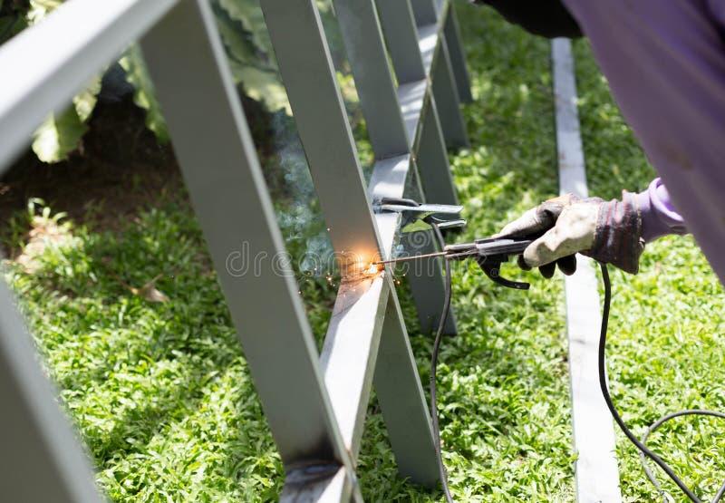 Trabajador que suelda con autógena barras de hierro de acero para una nueva cerca Frame foto de archivo libre de regalías