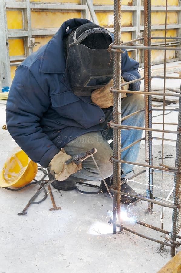 Trabajador que suelda un cedazo del metal en foto de archivo