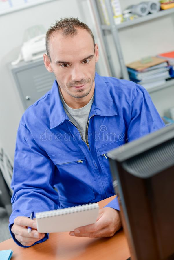 Trabajador que toma abajo de notas de la pantalla de ordenador imagen de archivo