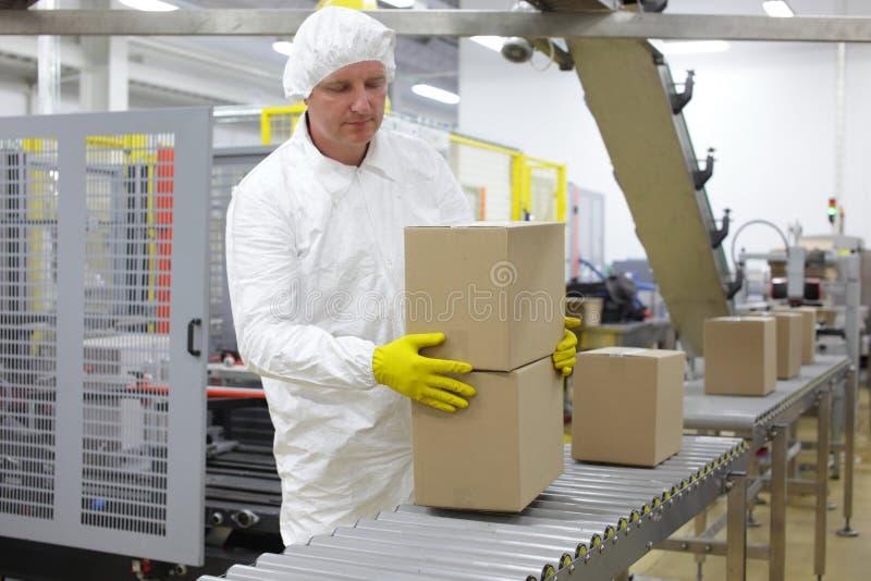 Trabajador que trabaja en línea de embalaje en fábrica fotografía de archivo