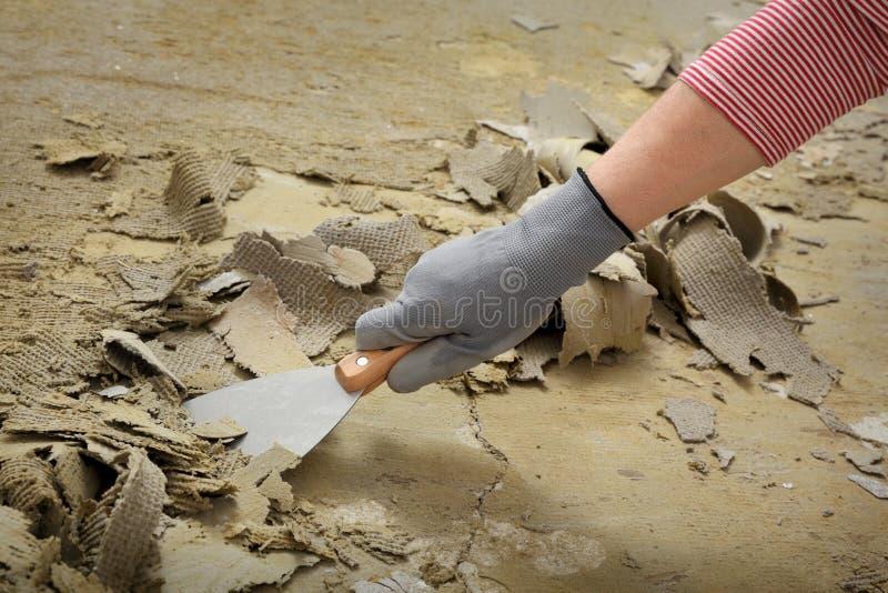Trabajador que usa el cuchillo de masilla para el piso de limpieza fotografía de archivo