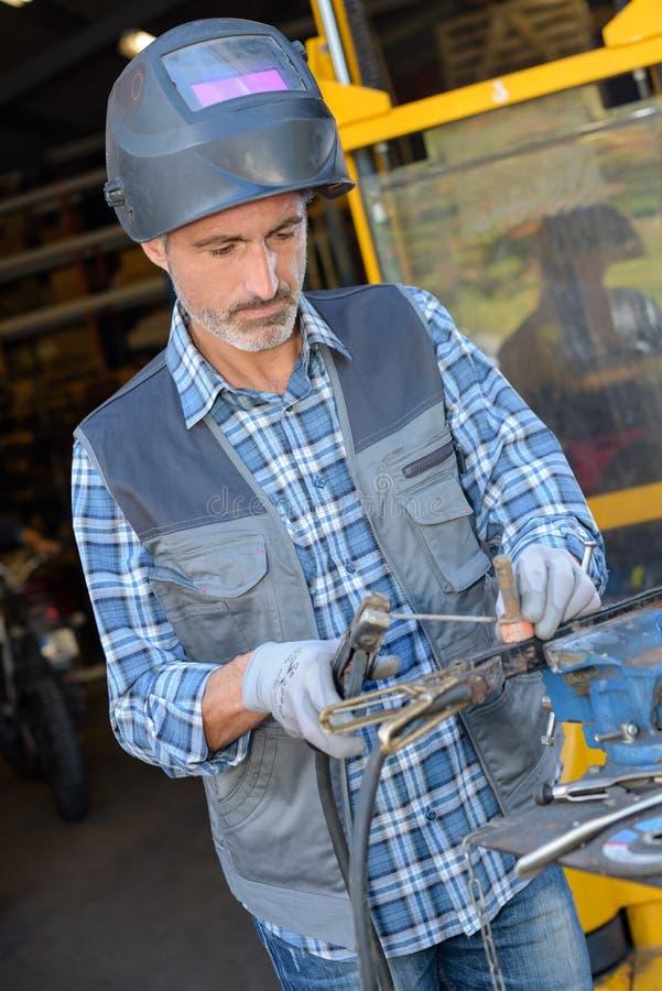 Trabajador que usa el hierro de la soldadura fotografía de archivo