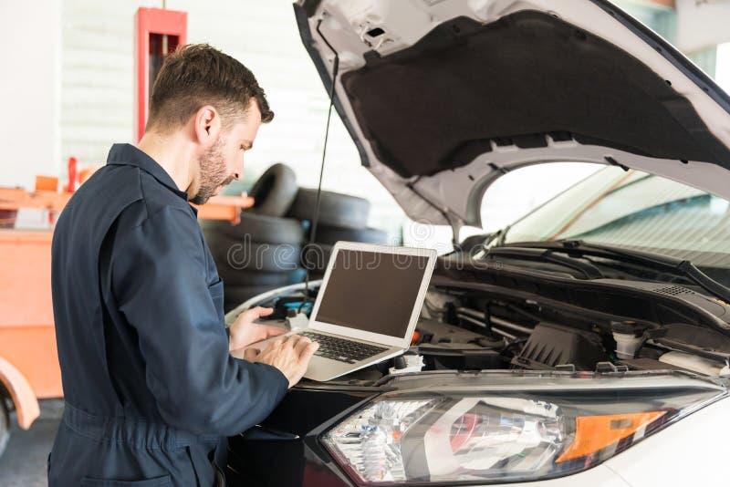 Trabajador que usa el ordenador portátil para detectar el malfuncionamiento en coche en el garaje imagen de archivo