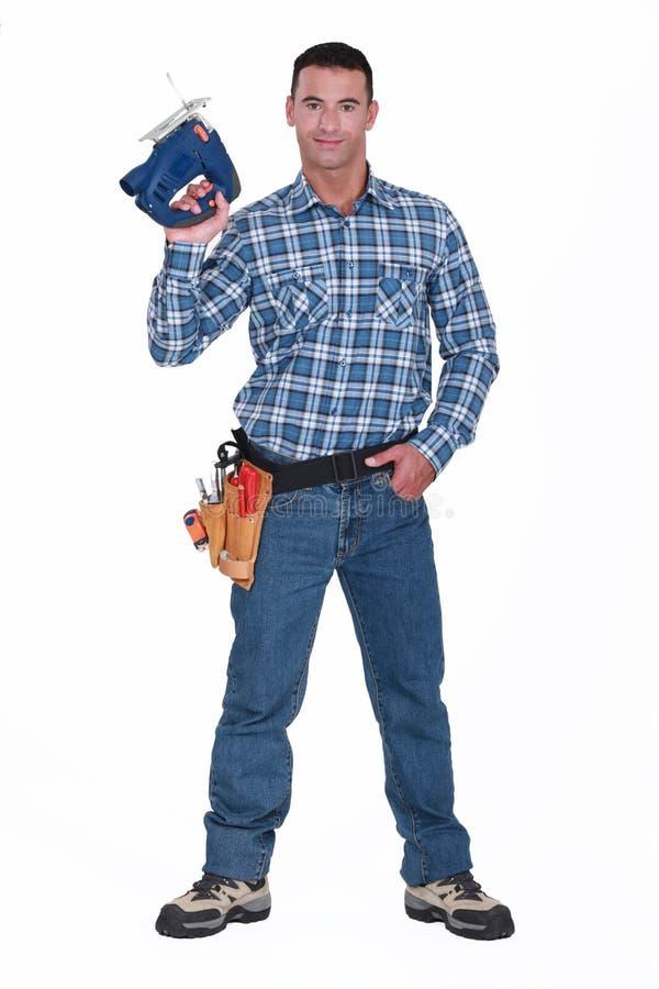 Trabajador que usa la sierra de cinta foto de archivo