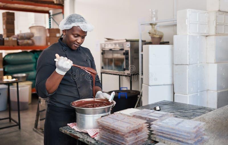 Trabajador que usa un baño maría para derretir el chocolate imagen de archivo