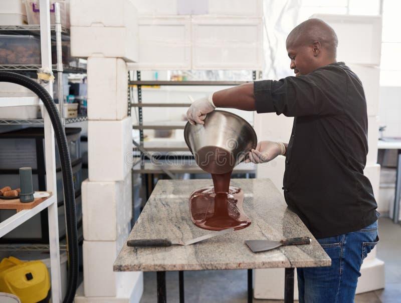 Trabajador que vierte el chocolate artesanal derretido hacia fuera en una tabla de la fábrica fotos de archivo