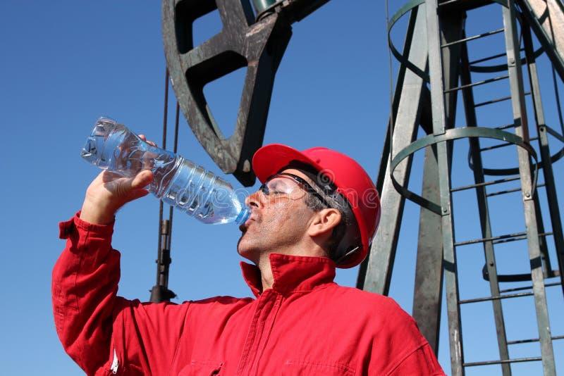 Trabajador sediento de la industria de petróleo. foto de archivo