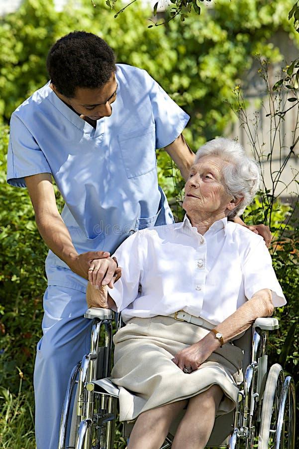 Trabajador sonriente de la atención sanitaria que habla con un mayor perjudicado foto de archivo libre de regalías