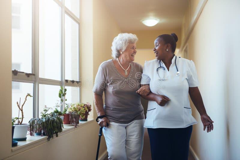 Trabajador sonriente de la atención sanitaria y mujer mayor que caminan junto imágenes de archivo libres de regalías