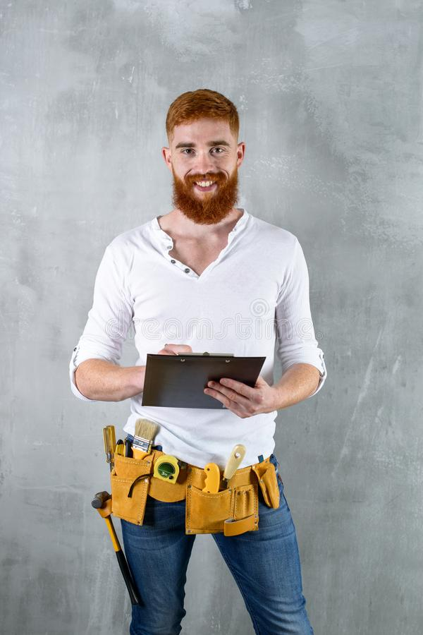 Trabajador sonriente del constructor que hace notas imagen de archivo libre de regalías