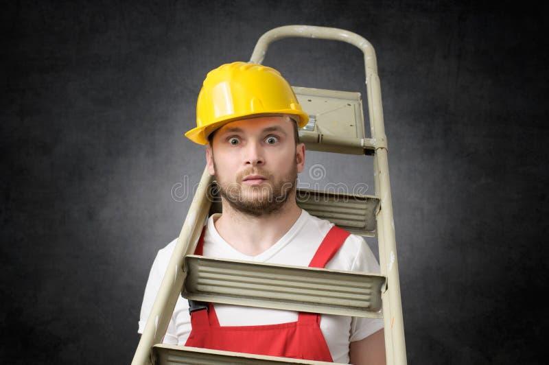 Trabajador torpe con la escalera imagen de archivo libre de regalías