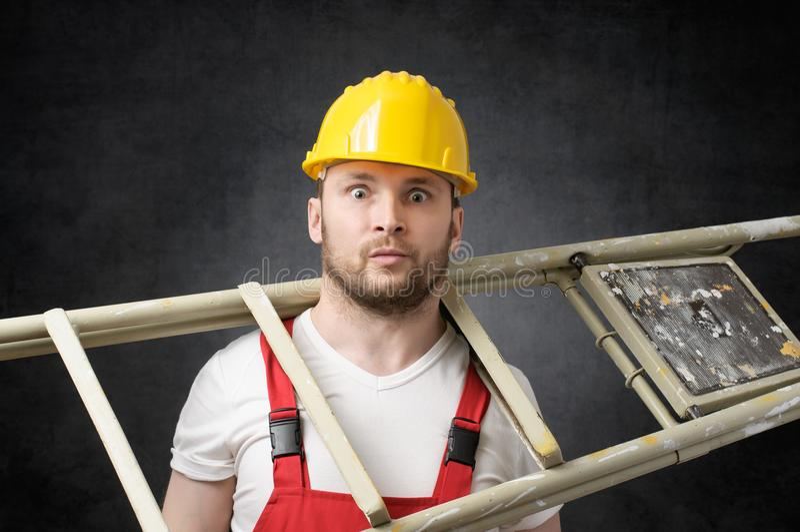 Trabajador torpe con la escalera foto de archivo libre de regalías