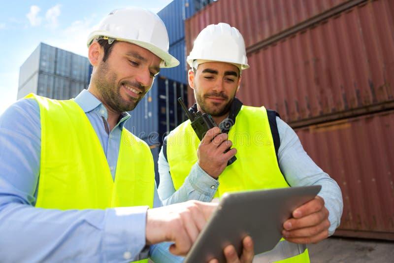 Trabajador y supervisor de muelle que comprueban datos de los envases sobre la tableta fotografía de archivo