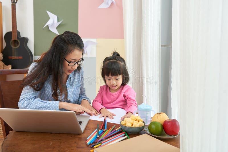 Trabajadora adulta con el ordenador portátil y la niña imagenes de archivo