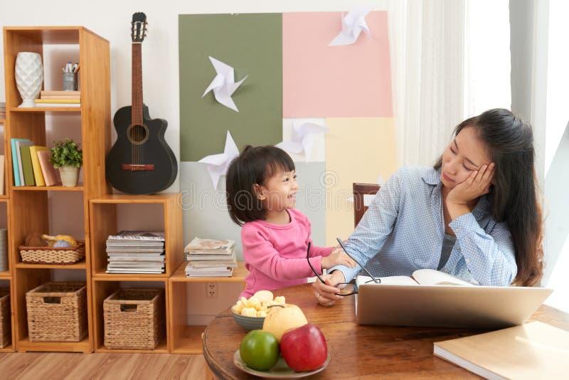 Trabajadora adulta con la muchacha juguetona en casa imagen de archivo