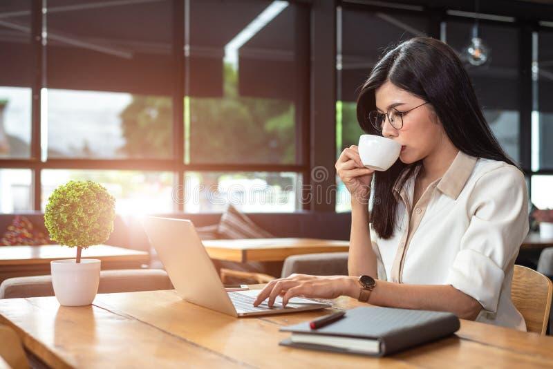 Trabajadora asiática usando el ordenador portátil y el café de consumición en café el PE imagenes de archivo