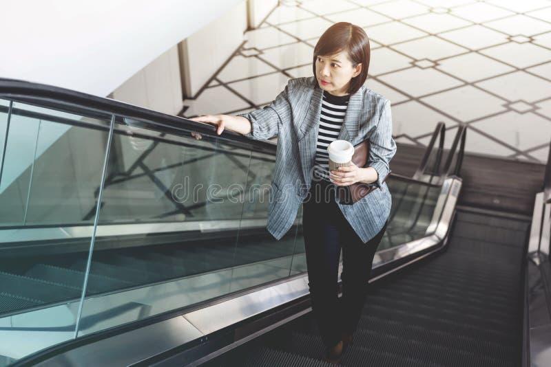 Trabajadora con la taza de café en la escalera móvil fotografía de archivo libre de regalías
