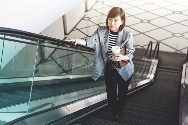 Trabajadora con la taza de café en la escalera móvil fotografía de archivo