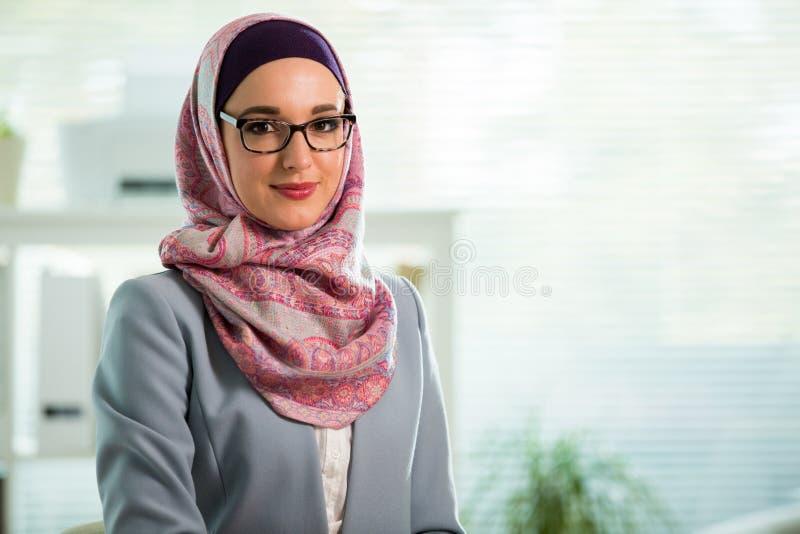 Trabajadora joven hermosa en hijab y lentes que sonr?en en oficina foto de archivo