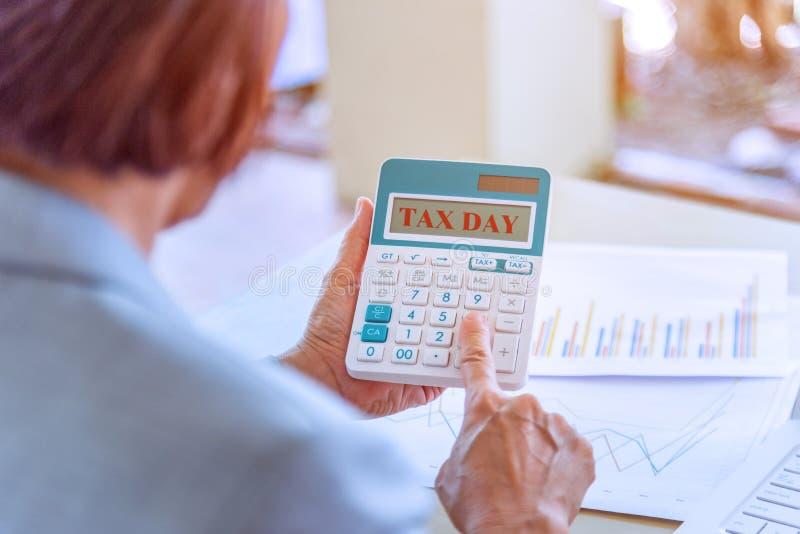 trabajadora mayor que sostiene la calculadora con palabras del día del impuesto y r imagen de archivo libre de regalías