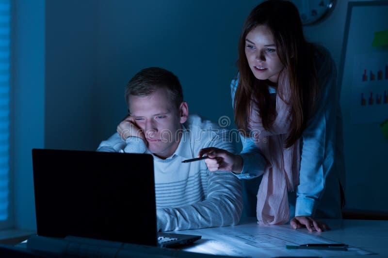 Trabajadores cansados que trabajan en horas extras imágenes de archivo libres de regalías