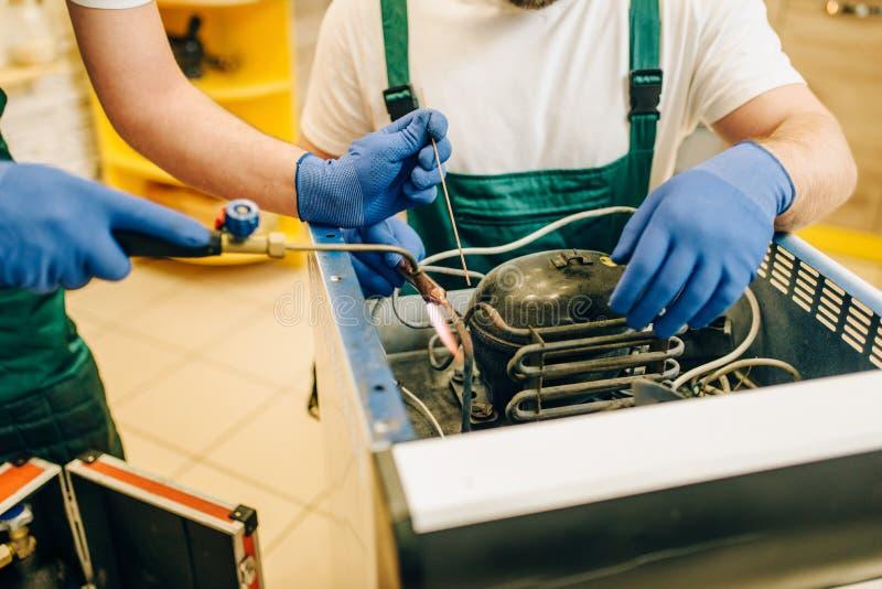 Trabajadores con el refrigerador de las reparaciones de la hornilla en casa foto de archivo