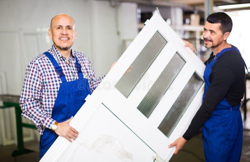 Trabajadores con las ventanas y las puertas del PVC fotografía de archivo libre de regalías