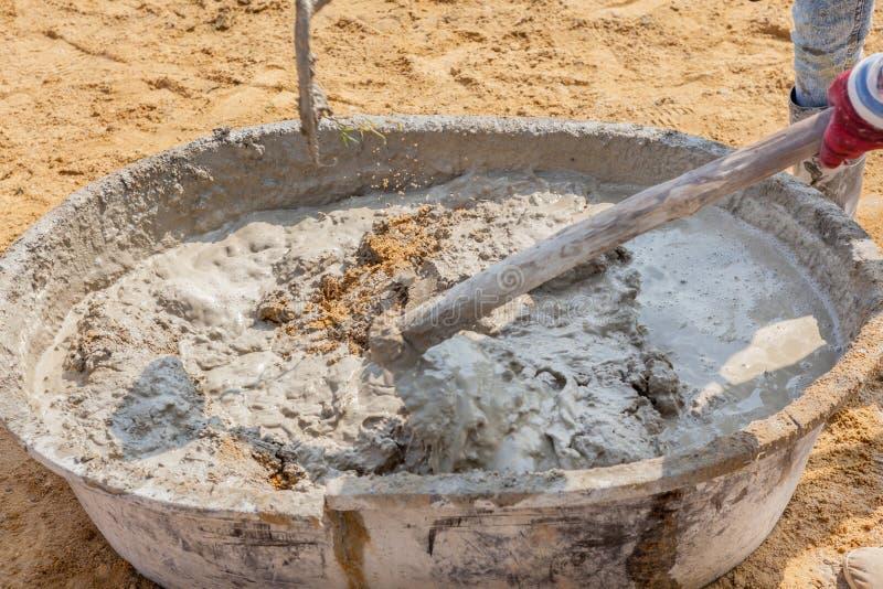 Trabajadores concretos que mezclan y que revuelven el cemento y la arena en salv fotos de archivo libres de regalías