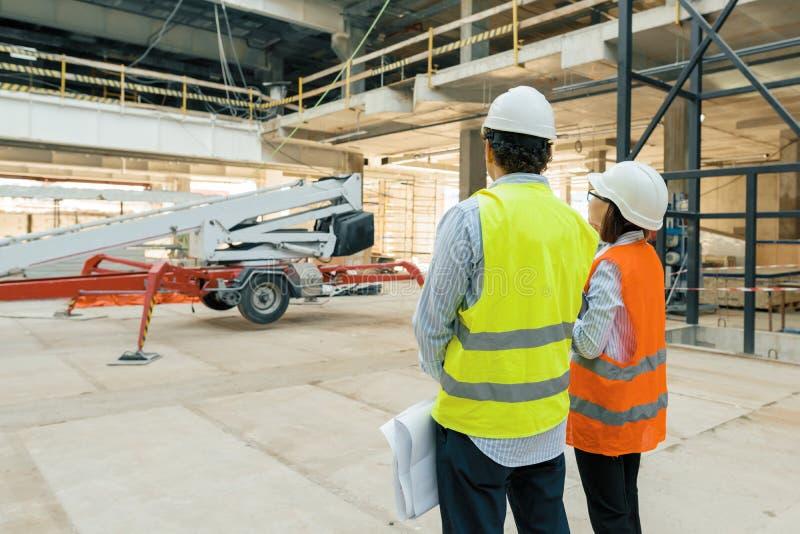 Trabajadores constructivos que trabajan en el emplazamiento de la obra, constructores que miran en el modelo, visión trasera, esp imagenes de archivo