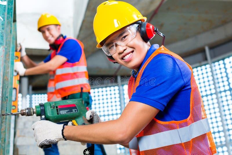 Trabajadores de construcción asiáticos que perforan en paredes del edificio imagen de archivo libre de regalías