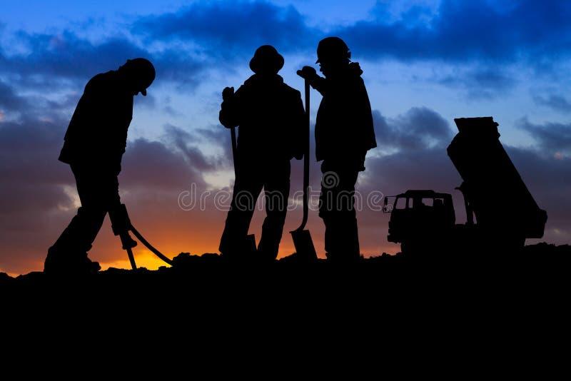 Trabajadores de construcción con el camión en la silueta de la puesta del sol fotografía de archivo