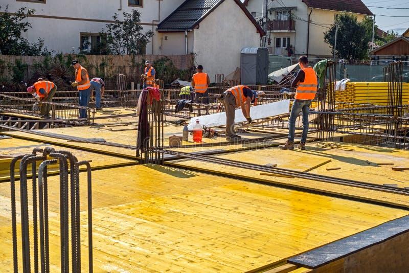 Trabajadores de construcción con los chalecos reflexivos que fabrican el rei de acero foto de archivo