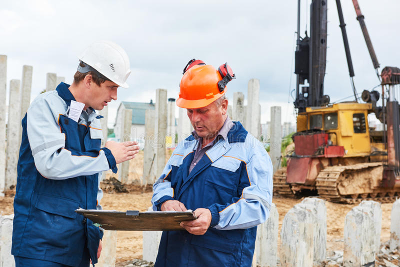 Trabajadores de construcción con proyecto delante de la máquina del conductor de pila fotografía de archivo
