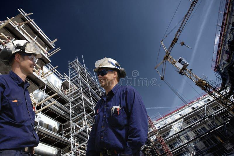 Trabajadores de construcción dentro del solar fotos de archivo