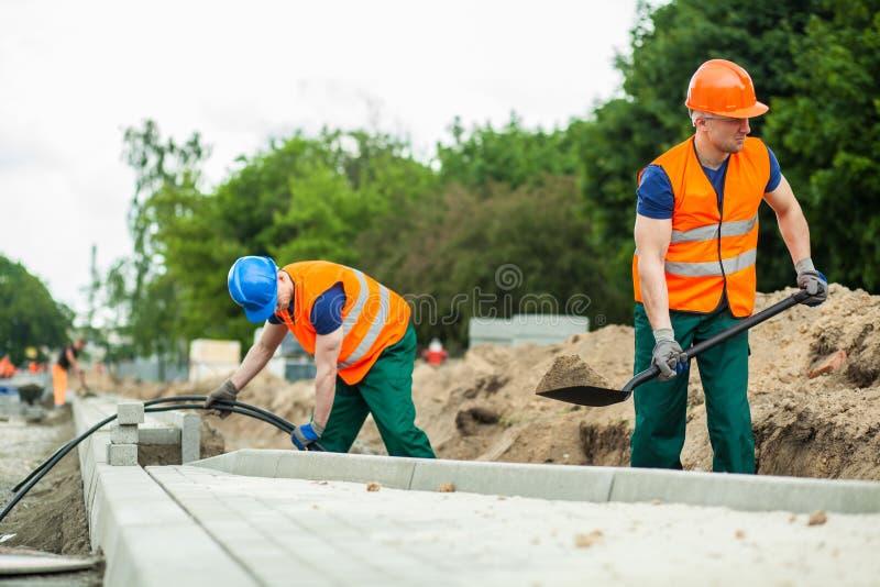Trabajadores de construcción durante su trabajo foto de archivo