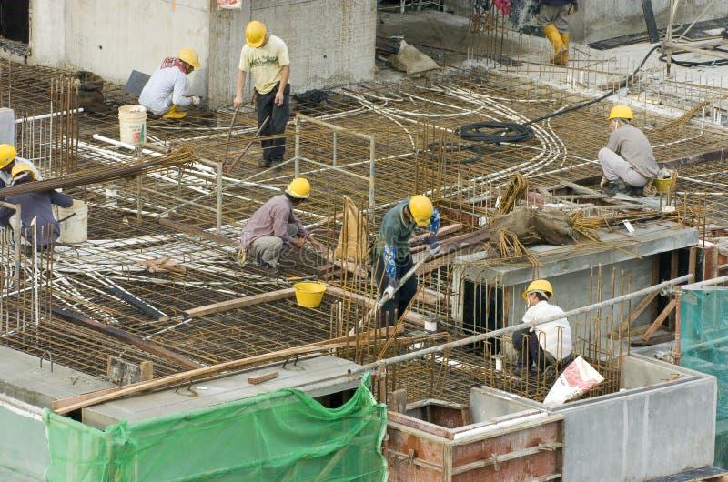 Trabajadores de construcción en el edificio alto fotografía de archivo