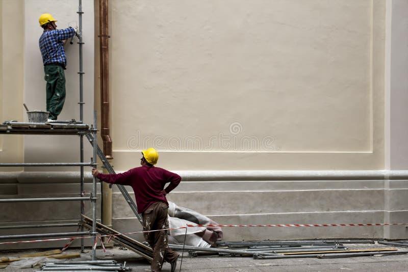 Trabajadores de construcción en la restauración del andamio del edificio viejo en Oldtown Vilna, Lituania - 20 de junio de 2016: imagenes de archivo