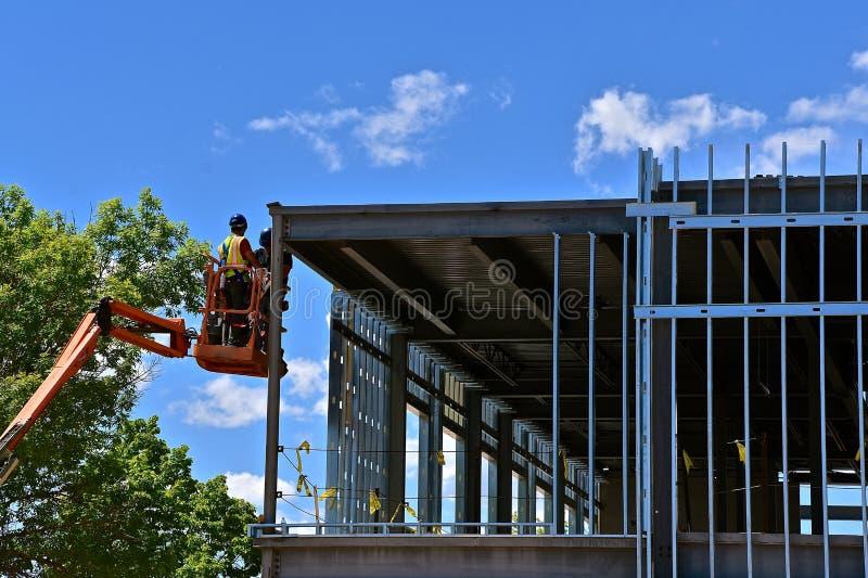 Trabajadores de construcción en una elevación en el solar fotos de archivo