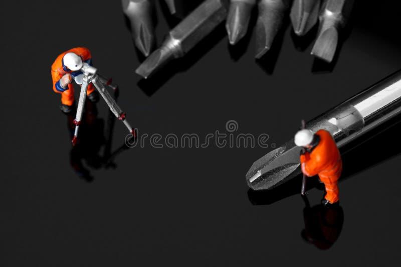 Trabajadores de construcción modelo con un destornillador y los pedazos fotos de archivo