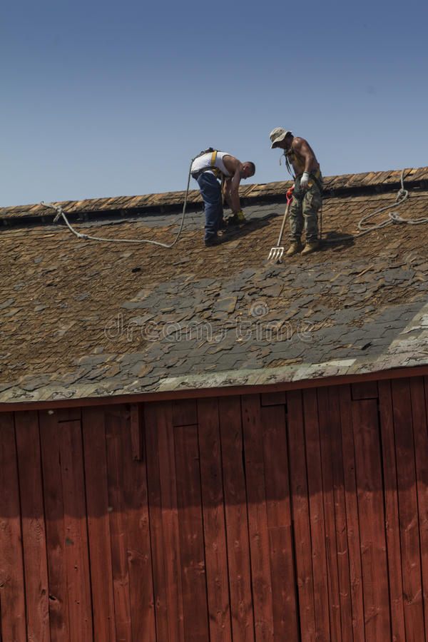 Trabajadores de construcción que cubren un granero fotografía de archivo