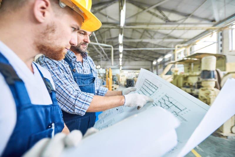 Trabajadores de construcción que examinan esquema eléctrico imágenes de archivo libres de regalías