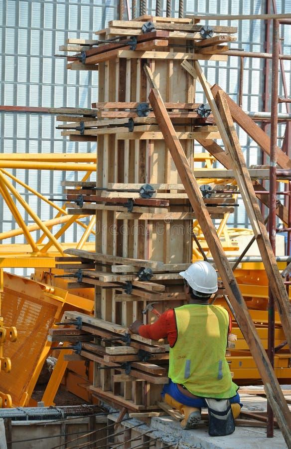 Trabajadores de construcción que fabrican encofrado de la columna de la madera en el emplazamiento de la obra fotos de archivo libres de regalías