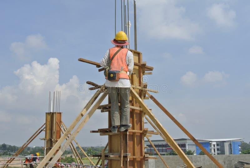 Trabajadores de construcción que fabrican encofrado de la madera de la columna imagen de archivo libre de regalías