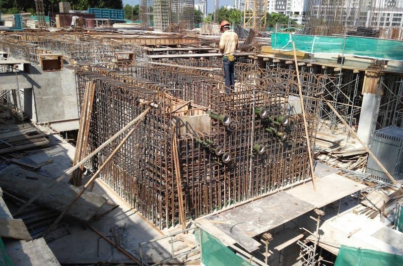 Trabajadores de construcción que fabrican la barra de acero del refuerzo dentro del encofrado de la madera en el emplazamiento de imagenes de archivo