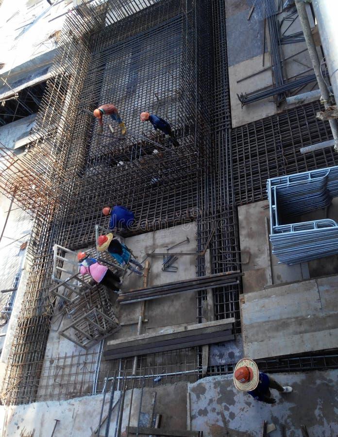 Trabajadores de construcción que fabrican la barra de acero del refuerzo dentro del encofrado de la madera en el emplazamiento de foto de archivo libre de regalías