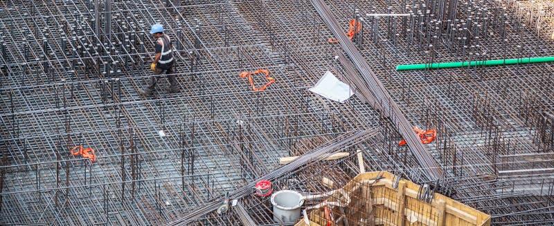 Trabajadores de construcción que fabrican la barra de acero del refuerzo en el emplazamiento de la obra fotografía de archivo