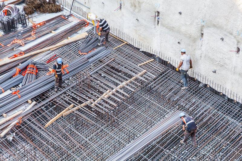 Trabajadores de construcción que fabrican la barra de acero del refuerzo en el emplazamiento de la obra fotos de archivo